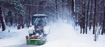 Tractor. Cleaning snow in winter Park Royalty Free Stock Photos