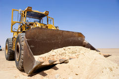 Tractor. Lifting sand on a desert Royalty Free Stock Images