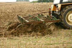 Tractor. Ploughing on field with storks in the background Stock Image