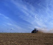 Tractor. Blue farm tractor pulling a plow in a farm field Stock Images