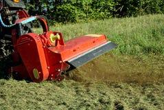 Tractor. Small farm tractor bush hogging on a grass field in Trentino Alto Adige. Italy Stock Image