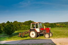 Tractor. Old tractor at sunset on green meadow Royalty Free Stock Images