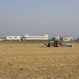 Tractor. In a file in autumn, buildings in background Stock Photography
