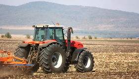 Tractor. A tractor working in a field with mountain background royalty free stock photos