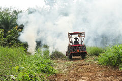 Tractor. S are wading into the smoke Stock Photography