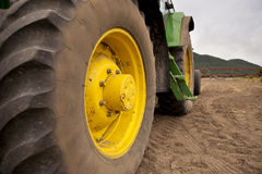 Tractor. An agricultural tractor with big wheels parked on naked soil during a cloudy day Royalty Free Stock Photo