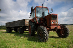Tractor. Red tractor with trailer  on field Royalty Free Stock Image