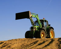 Tractor. On a field with blue sky Royalty Free Stock Image