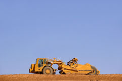 Tractor. Large yellow tractor leveling dirt Stock Photos