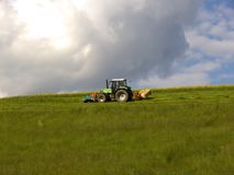 Tractor. Green tractor mowing a meadow stock photos
