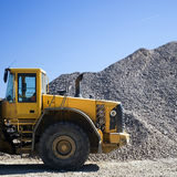 Tractor. Yellow tractor truck parked in front of a pile of rocks Stock Images
