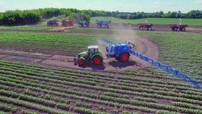 Tractor agrícola con el remolque de rociadura que fertiliza el campo agrícola almacen de metraje de vídeo