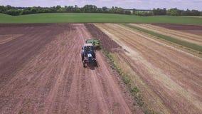 Tractor agrícola con el remolque para arar el trabajo en campo arable almacen de video
