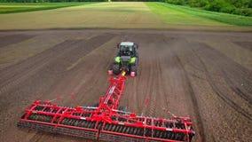 Tractor agrícola con el remolque que ara en campo de cultivo Sector agrícola almacen de video