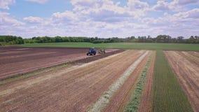 Tractor agrícola con el remolque que trabaja en campo de cultivo Sector agrícola almacen de metraje de vídeo
