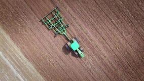 Tractor agrícola que ara el campo arable Vista aérea de la maquinaria de la agricultura metrajes
