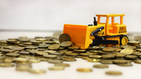 Tractor amarillo que rastrilla encima de monedas Rublo rusa Imagenes de archivo