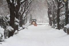Tractor anaranjado que conduce abajo de nieve en un callejón del parque Imagen de archivo libre de regalías