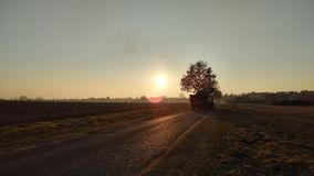 Tractor antes de una puesta del sol fotografía de archivo