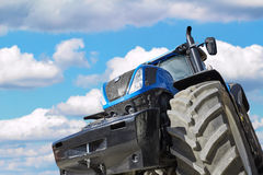 Tractor on a background cloudy sky. Tractor working on the farm, a modern agricultural transport, a farmer working in the field, tractor in the background cloudy Stock Photo