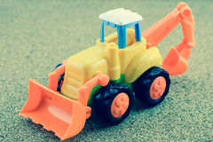 Tractor backhoe toy on sand background. Stock Images