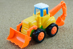 Tractor backhoe toy on sand background. Royalty Free Stock Image