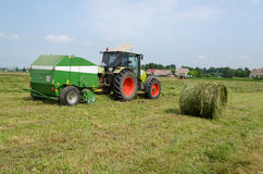 Tractor bailer collect hay in agriculture field Royalty Free Stock Photos