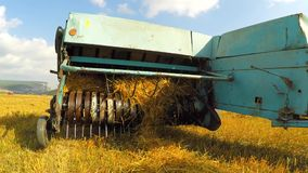 Tractor Baler Collecting Straw Left By Combine At. CLOSE UP: Video shot of a light blue farm tractor with machanized trailer slowly moving across golden stubble stock video