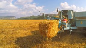 Tractor Baler Discharging Fresh Bale During. This is a shot of a tractor baler at trailer discharging fresh wheat bale during harvesting while moving at the stock footage