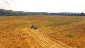 Tractor Baler Driving In Stubble Field. This is an aerial shot over golden stubble field with a light blue farm tractor baler slowly moving along. There are some stock video