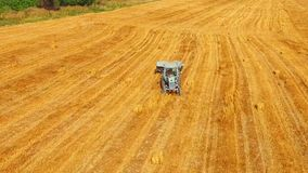 Tractor Baler Moving Across Yellow Stubble Field. This is an aerial shot over golden stubble field with a light blue farm tractor baler slowly driving across it stock footage