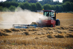 Tractor baling straw in a field Stock Photography