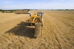 Tractor baling straw in sunny, rural field Royalty Free Stock Photos