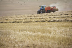 Tractor baling straw in sunny, rural field Stock Photography