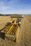 Tractor baling straw in sunny, rural field Stock Photos