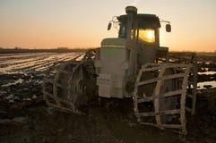 Tractor bij zonsondergang op het padieveld stock foto