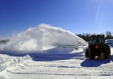 Tractor blowing snow after a storm. Farm tractor blowing snow after a Blizzard royalty free stock image