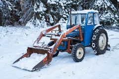 Tractor. A blue tractor coverd in snow ready to plow Royalty Free Stock Image