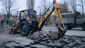 Tractor bucket breaks asphalt. Bila Tserkva, Ukraine 20 april 2018: - Old tractor bucket moves pieces of broken asphalt. Tractor removes broken asphalt stock video footage