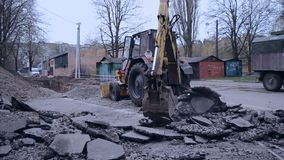 Tractor bucket breaks asphalt. Bila Tserkva, Ukraine 20 april 2018: - Old tractor bucket moves pieces of broken asphalt. Tractor removes broken asphalt stock footage