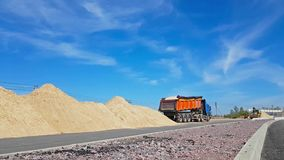 Tractor bucket loads heavy truck with sand. Heavy Tractor loads truck with sand using bucket. Construction of high-speed bypass road around Krasnoe Selo, Saint stock footage