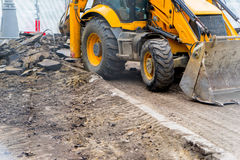 Tractor with bucket performs road works Stock Images