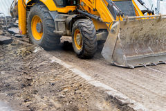 Tractor with bucket performs road works stock image