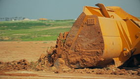 Tractor with a bulldozer moving soil at a construction site.  stock footage