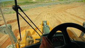 Tractor with a bulldozer moving soil at a construction site. View from the tractor