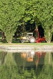 Tractor and bushy under trees Royalty Free Stock Photo