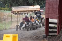Tractor carrying people in cow toy train cars up the dirt road stock photography