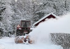 Tractor casting snow against over a fence Stock Photography