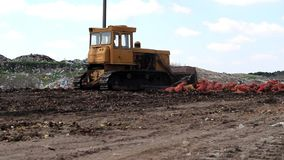 Tractor in the city dump. The tractor is leveling the area of the municipal waste dump stock video