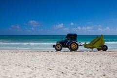 Tractor cleaning the beach from algae in the morning. Playa del Stock Photography